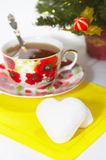 Treacle cake in form heart. White treacle cake in form heart with cup of tea on background fir tree Stock Photo