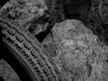 The Tread of a Hard Rubber Tyre. A Hard Rubber Tyre Grip, Showing the Tread and Shapes of the Moulding, on a Blurred Rock and Stone Background royalty free stock photography