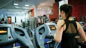 Treadmill, αθλητικό νέο κορίτσι πηγαίνει μέσα για τον αθλητισμό, καρδιο κατάρτιση, νέο τρέξιμο γυναικών, το κορίτσι είναι δεσμευμ φιλμ μικρού μήκους