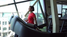 Ελκυστικό καυκάσιο κορίτσι που τρέχει treadmill στην αθλητική γυμναστική με το τηλέφωνο και τα ακουστικά Κάμερα σε 4K απόθεμα βίντεο