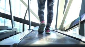 Ελκυστικό καυκάσιο κορίτσι που τρέχει treadmill στην αθλητική γυμναστική με το τηλέφωνο και τα ακουστικά Κάμερα το 1920 Ñ… 1080 Α απόθεμα βίντεο
