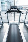 Treadmill against big window, gym interior, nobody. Jogging track, stationary running simulator, sport equipment in fitness club Royalty Free Stock Images