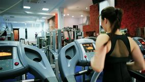 Treadmill, athletic young girl goes in for sports, cardio training, young woman running, girl is engaged on a simulator. In the gym, sport for slender figure stock footage