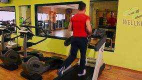 Treadmill. Man at the gym. Brawny man doing workout at the gym stock video footage