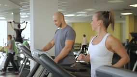 On treadmill man and a woman start running on treadmill in gym. In fitness club young people with smile walk and then accelerate during training on sports stock video
