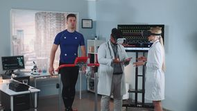 During the treadmill test two mixed race doctors in VR glasses speaking about something. While athlete walking on racetrack. In Scientific Sports Laboratory stock footage