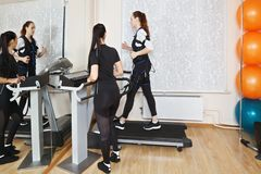 Treadmill training. Caucasian women training on treadmill in gym. Female trainer standing aside manages electric muscle stimulation purposed to increase Royalty Free Stock Photo