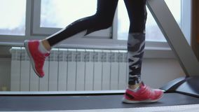 Treadmill. Young sportswoman in training at the gym. Side view.  stock video footage