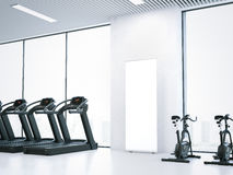 Treadmills, bicycle simulators and blank roll-up bunner. 3d rendering. Treadmills, bicycle simulators and blank roll-up bunner in bright interior. 3d rendering Stock Images