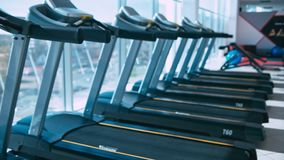 Treadmills in gym. Horizontal panning. Shallow depth of field stock video