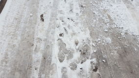 Treads and footprints in snow, city street covered in snow. Steadicam shot stock video