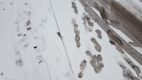 Treads and footprints in snow, city street covered in snow. Steadicam shot stock footage