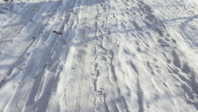 Treads and footprints in snow, city street covered in snow. Steadicam shot stock video footage