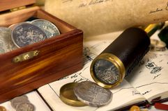 Treasure. An adventurous scene of exploration. Filled with maps, spanish silver, and a trusty telescope. Could this be desk of a captain, or a pirate perhaps Stock Image