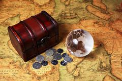Treasure box and globe on ancient map background Stock Photos