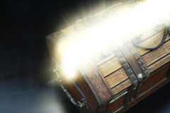 Treasure Chest. A close-up on an open antique wooden box with light shining from within royalty free stock photos