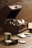 Treasure chest. Old coins on wooden table Stock Images