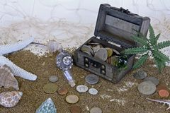 Treasure chest on beach and coins beside it stock photo
