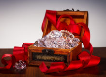 Treasure chest with diamonds. Many diamonds in a treasure chest with a red ribbon stock image