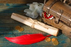 Treasure chest end scroll tied a rope on a wooden table. Treasure chest end vintage paper roll is tied up by a rope on an old wooden table, near a roll is the royalty free stock image