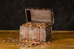 Treasure chest with with euro coins. Full wooden treasure chest with a light background and euro coins standing on an old table stock image