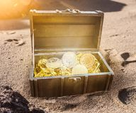 Treasure chest filled with bitcoins surrounded by golden glow partially burried in sand Stock Photography