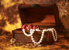 Treasure chest full of jewelry. And pearl bracelet Stock Images