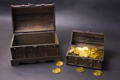 Treasure chest with gold. Coins in front of dark background royalty free stock images