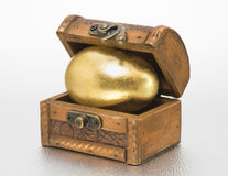 Treasure chest with golden egg. Wooden treasure chest with golden egg Stock Images
