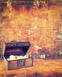 Treasure chest with jewelry inside. Against grunge background Stock Photos