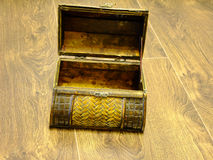 Treasure Chest. Little brown Treasure Chest opened on a dark wooden Floor Stock Photos