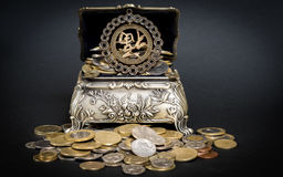 Treasure chest. Little metal chestfilled up with coins bringing good fortune Stock Image