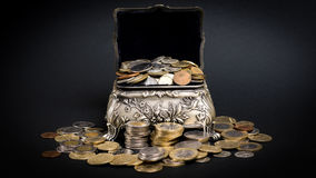 Treasure chest. Little metal chest filled up with coins bringing good fortune Stock Photo