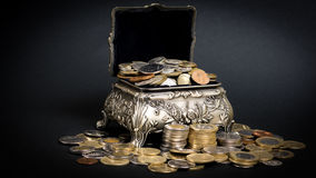 Treasure chest. Little metal chest filled up with coins bringing good fortune Stock Photography