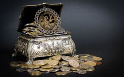 Treasure chest. Little metal chest filled up with coins bringing good fortune Royalty Free Stock Photo