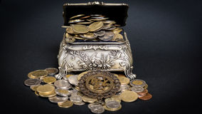 Treasure chest. Little metal chest filled up with coins bringing good fortune Stock Photos