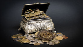 Treasure chest. Little metal chest filled up with coins bringing good fortune Royalty Free Stock Images