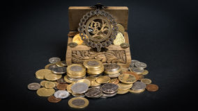Treasure chest. Little wooden chest filled up with coins bringing good fortune Stock Photography