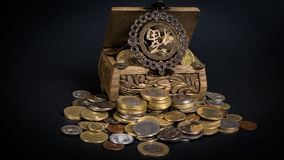 Treasure chest. Little wooden chest filled up with coins bringing good fortune Stock Images