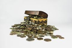 Treasure chest which is bursting with coins on a white backgroun Stock Images