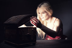 Treasure chest. Young blond woman securing her treasure in a retro wooden chest royalty free stock photo