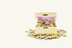 Treasure coins box. Tresure box with overflow coins all around the box on the white background royalty free stock image