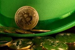 Pile of bitcoins inside green hat St Patricks Day. Treasure of golden bitcoins inside a green velvet hat on wooden table to celebrate luck on St Patrick`s Day of Stock Image