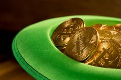 Pile of bitcoins inside green hat St Patricks Day. Treasure of golden bitcoins inside a green velvet hat on wooden table to celebrate luck on St Patrick`s Day of Royalty Free Stock Photography
