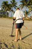 Treasure hunter. An older man hunts for lost treasure on the beach by using a metal detector stock photo