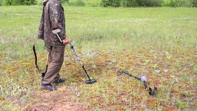Treasure hunter in the field with a metal detector. And a shovel in search of treasure and jewelry, archeology as a hobby, search for historical heritage stock video footage