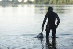 Treasure hunter is looking for a metal detector in the river. Treasure hunter Royalty Free Stock Image