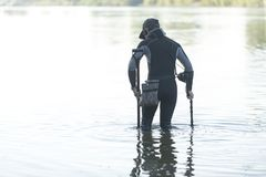 Treasure hunter is looking for a metal detector in the river. Treasure hunter, treasure hunter is looking for a metal detector in the river Royalty Free Stock Images