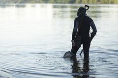 Treasure hunter is looking for a metal detector in the river. Treasure hunter treasure hunter is looking for a metal detector in the river Royalty Free Stock Image