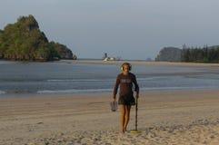 Treasure hunter with Metal detector on the beach stock image